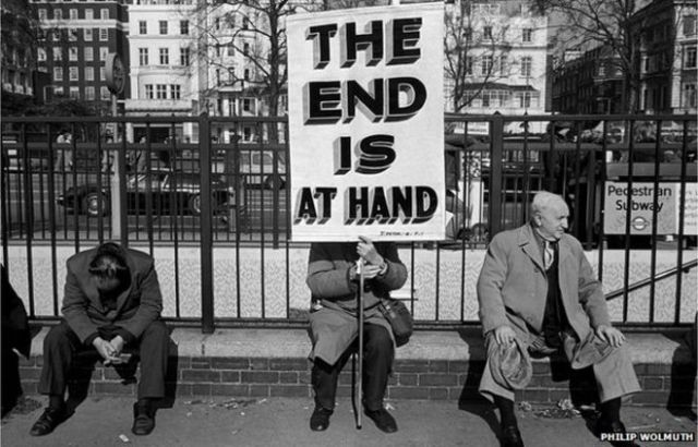 """Street preacher with """"end of the world"""" sign."""