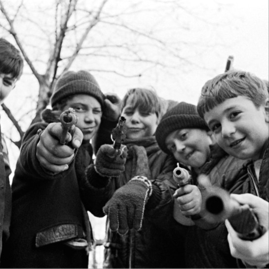 Boys pointing toy guns at camera