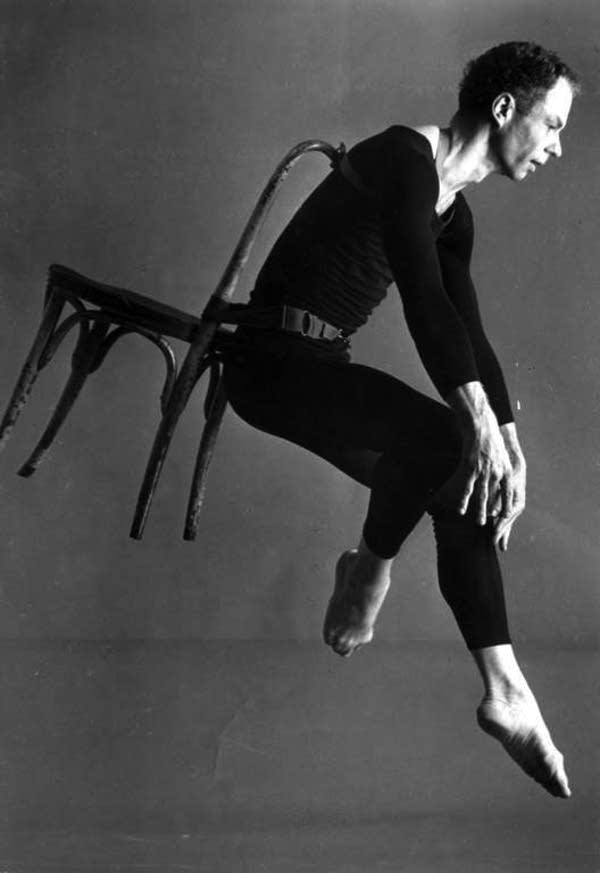 Merce Cunningham with a chair on his back