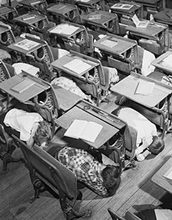 children hiding under school desks in 1950s nuclear drill