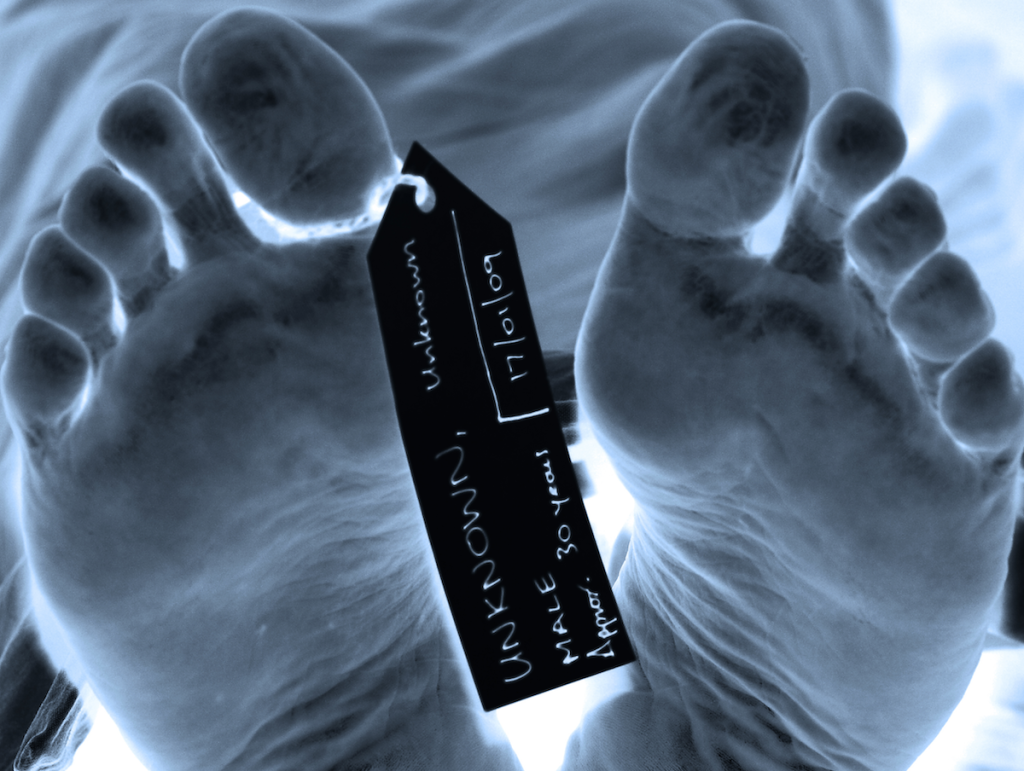 Dead man's feet in morgue with toe tags.