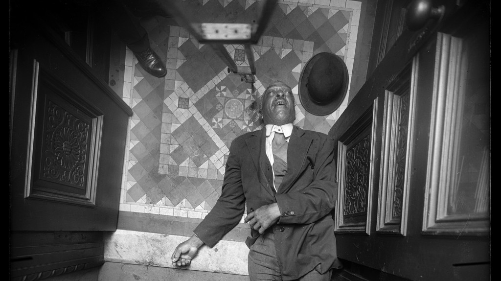 Dead Black man on the floor in New York City in the early 20th century.