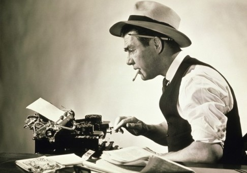 Vintage newspaperman at typewriter.