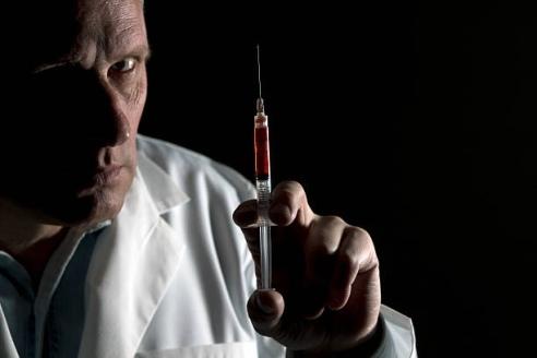 Evil doctor  with blood filled syringe