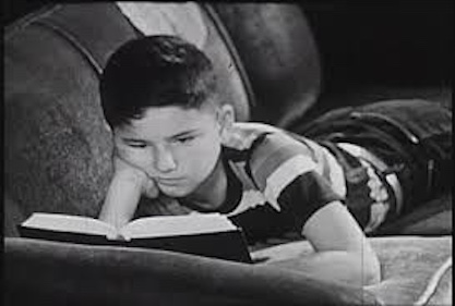 Vintage photo of young boy reading