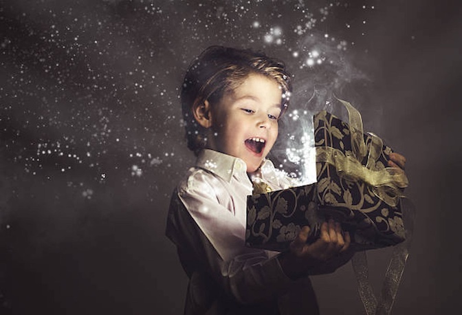 Young boy opening a glowing box