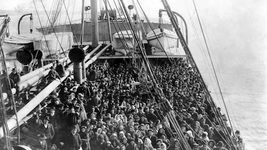 Immigrants on ship deck in New York harbor