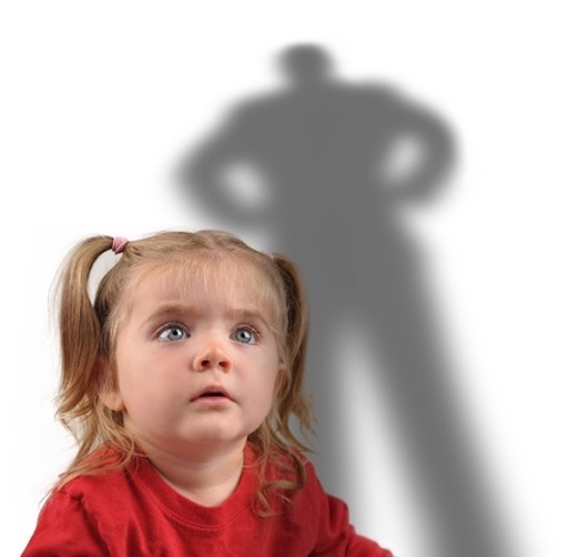 Frightened little girl looking up at shadow